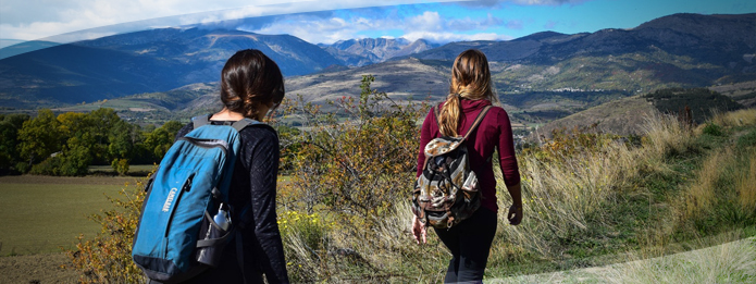 Individuals with backpack with hills and mountains